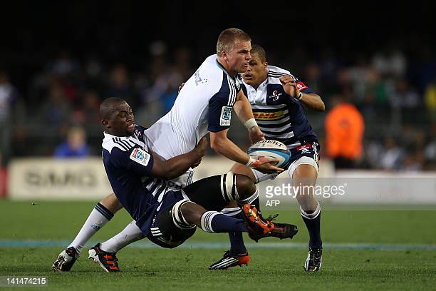 Gareth Anscombe of The Blues offloads as he is tackled by Siya Kolisi of The Stormers and Eben Etzebeth of The Stormers on March 16 2012 during the...
