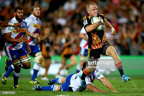 Gareth Anscombe of the Chiefs evades the tackle of Jozua Francois Malherbe of the Stormers during the round five Super Rugby match between the Chiefs...