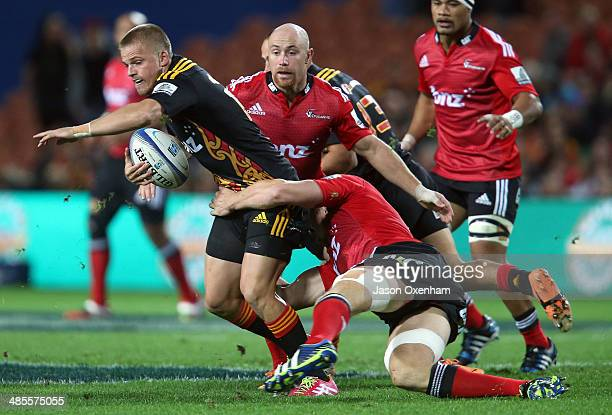 Gareth Anscombe of the Chiefs looks for support in the tackle of Kieran Read of the Crusaders during the Chiefs and Crusaders Super Rugby match at...
