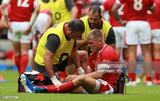 Gareth Anscombe of Wales receives attention to a leg injury during the Quilter International match between England and Wales at Twickenham Stadium on...