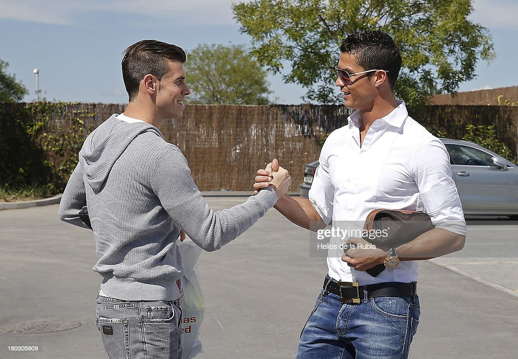 Gareth Bale (L) and Cristiano Ronaldo of Real Madrid shake hands before a training session at Valdebebas training ground on September 11, 2013 in Madrid, Spain.