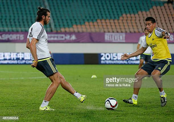 Gareth Bale and James Rodriguez of Real Madrid warm up during a training session at Tianhe Stadium training ground on July 26 2015 in Guangzhou China