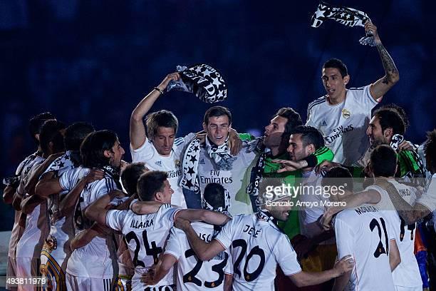 Gareth Bale celebrates with teammates Fabio Coentrao Angel Di Maria and Nacho Fernandez during the Real Madrid celebration the day after winning the...