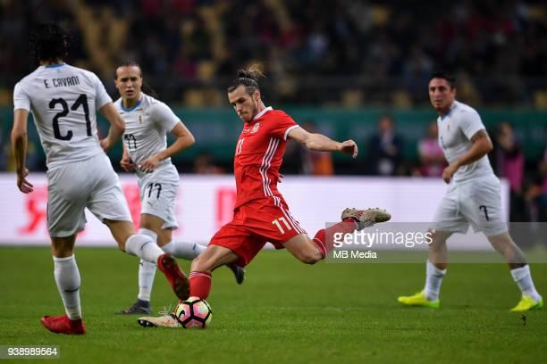 Gareth Bale center of Wales national football team kicks the ball to make a shoot against players of Uruguay national football team in their final...