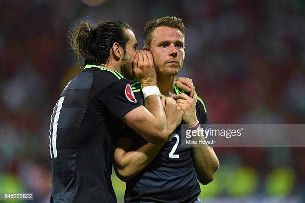 Gareth Bale consoles teammate Chris Gunter of Wales after defeat in the UEFA EURO 2016 semi final match between Portugal and Wales at Stade des...