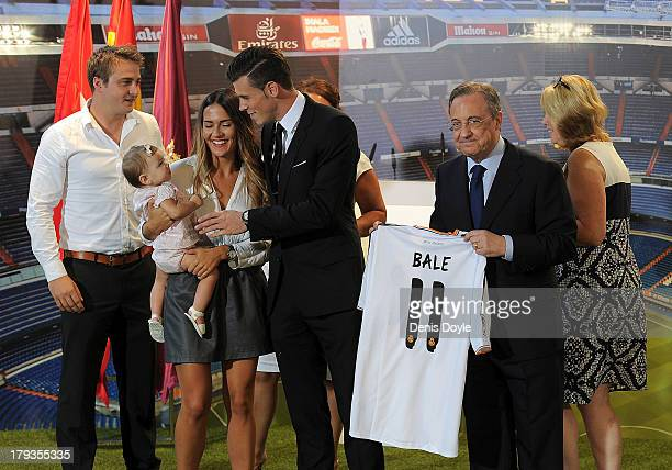 Gareth Bale holds up his new Real Madrid shirt with Real President Florentino Perez alongside friend Ellis Randall and family including daughter Alba...