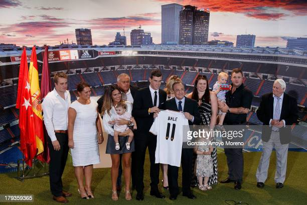 Gareth Bale holds up his new Real Madrid shirt with Real President Florentino Perez and family including girlfriend Emma Rhys Jones and daughter Alba...