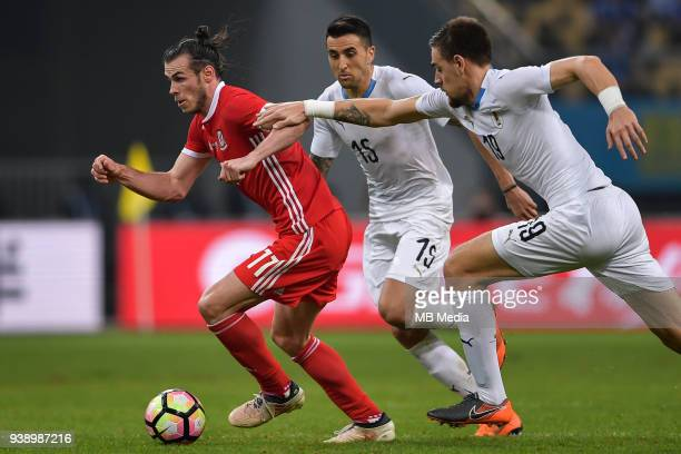 Gareth Bale left of Wales national football team kicks the ball to make a pass against players of Uruguay national football team in their final match...