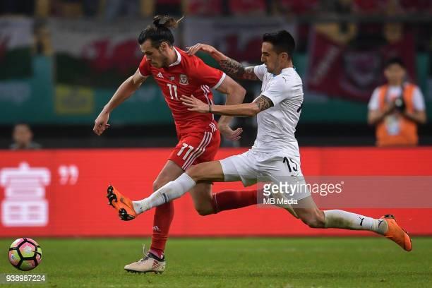 Gareth Bale left of Wales national football team kicks the ball to make a pass against Matias Vecino of Uruguay national football team in their final...