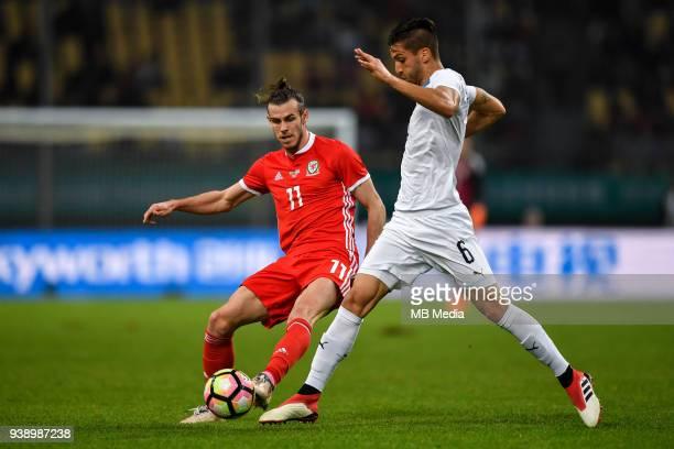Gareth Bale left of Wales national football team kicks the ball to make a pass against Rodrigo Bentancur of Uruguay national football team in their...