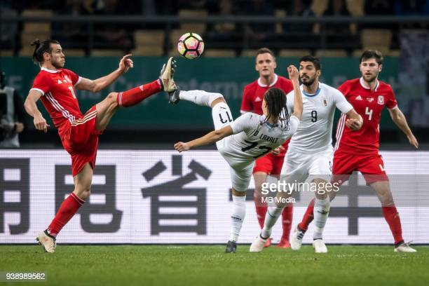 Gareth Bale left of Wales national football team kicks the ball to make a pass against Diego Laxalt of Uruguay national football team in their final...
