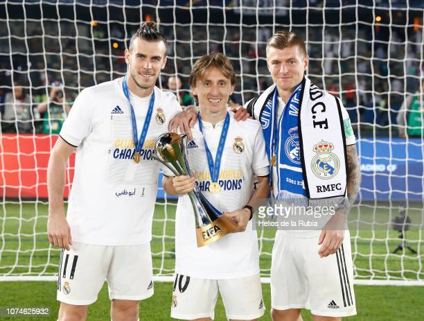 Gareth Bale Luka Modric and Toni Kroos of Real Madrid poses with the trophy after the match between Real Madrid and Al Ain on December 22 2018 in Abu...