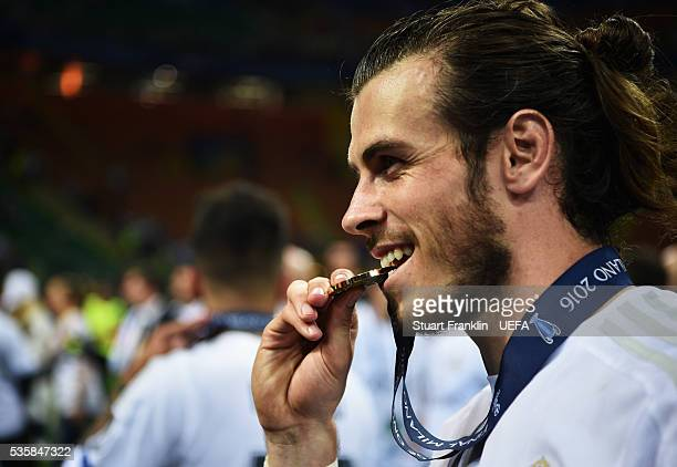 Gareth Bale of Madrid bites his winners medal after the UEFA Champions League Final match between Real Madrid and Club Atletico de Madrid at Stadio...