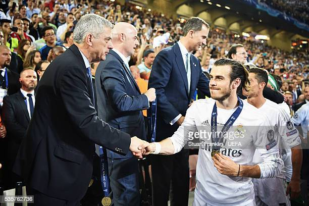 Gareth Bale of Madrid is congratulated by Ángel María Villar Llona, first vice president of UEFA after the UEFA Champions League Final match between...