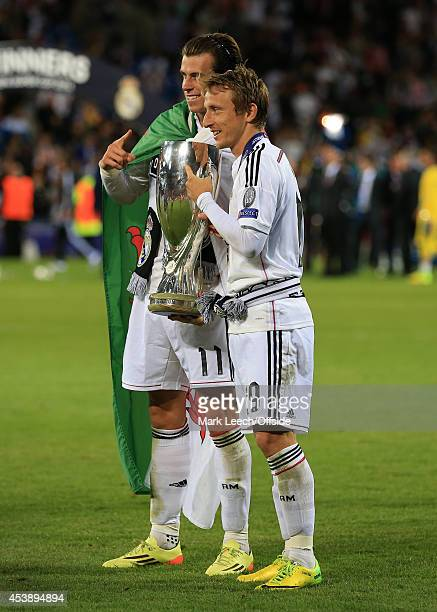 Gareth Bale of Real Madrid and teammate Luka Modric celebrate with the trophy following victory in the UEFA Super Cup match between Real Madrid and...