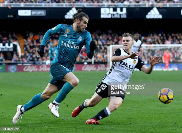 Gareth Bale of Real Madrid and Toni Lato of Valencia chase the ball during the La Liga match between Valencia and Real Madrid at Estadio Mestalla on...