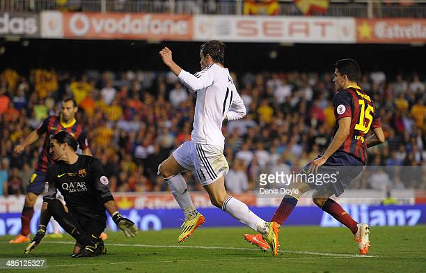 Gareth Bale of Real Madrid beats Marc Bartra and Jose Pinto of Barcelona to score Real's 2nd goal during the Copa del Rey Final between Real Madrid...