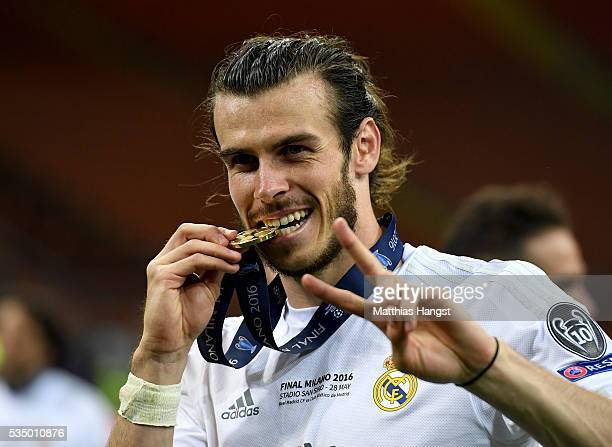 Gareth Bale of Real Madrid celebrates by biting his winners medal and gestures that it is his second time winning it after the UEFA Champions League...