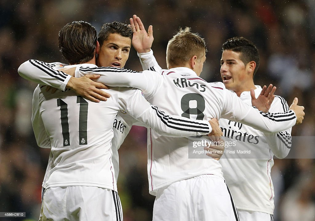 Gareth Bale (L) of Real Madrid celebrates with Cristiano Ronaldo (2L), Toni Kroos (2R) and James Rodriguez after scoring the opening goal during the La Liga match between Real Madrid and Rayo Vallecano at Estadio Santiago Bernabeu on November 8, 2014 in Madrid, Spain.