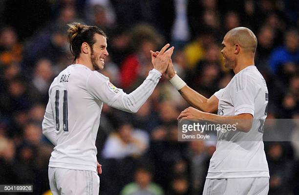 Gareth Bale of Real Madrid celebrates with team mate Pepe as he scores their third goal during the La Liga match between Real Madrid CF and RC...