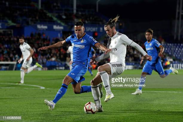 Gareth Bale of Real Madrid CF competes for the ball with Bruno Gonzalez Cabrera of Getafe CF during the La Liga match between Getafe CF and Real...