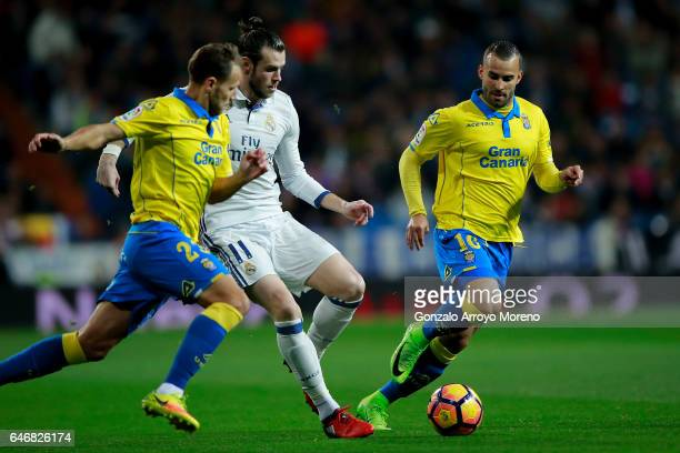 Gareth Bale of Real Madrid CF competes for the ball with Jese Rodriguez of UD Las Palmas and his teammate Daniel Castello during the La Liga match...