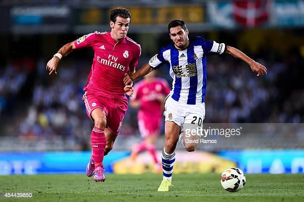 Gareth Bale of Real Madrid CF competes for the ball with Joseba Zaldua of Real Sociedad during the La Liga match between Real Sociedad de Futbol and...