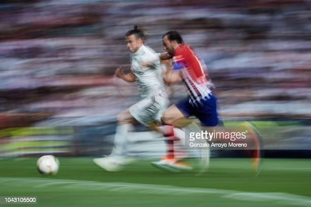 Gareth Bale of Real Madrid CF competes for the ball with Juan Francisco Torres alias Juanfran of Atletico de Madrid during the La Liga match between...