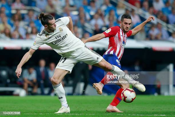 Gareth Bale of Real Madrid CF competes for the ball with Koke of Atletico de Madrid during the La Liga match between Real Madrid CF and Club Atletico...