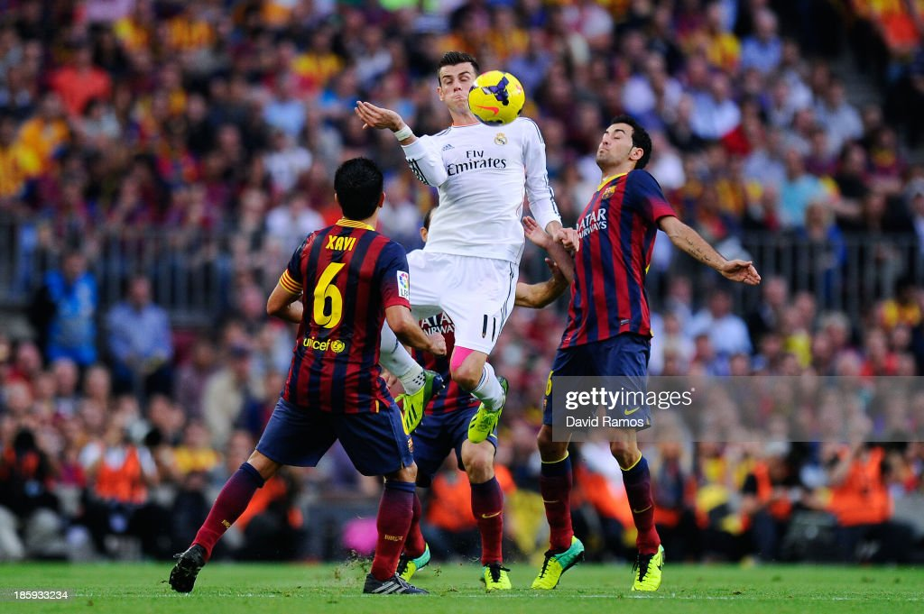Gareth Bale of Real Madrid CF duels for the ball with Sergio Busquets of FC Barcelona during the La Liga match between FC Barcelona and Real Madrid CF at Camp Nou on October 26, 2013 in Barcelona, Spain.