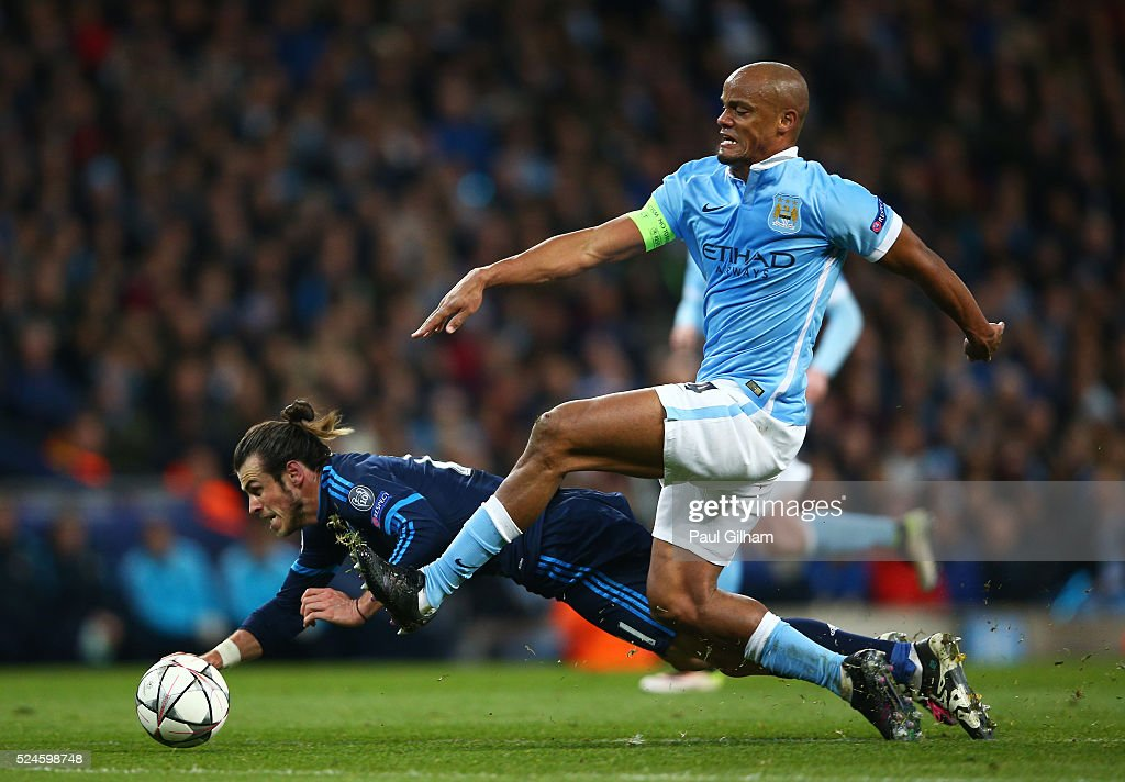 Gareth Bale of Real Madrid CF goes down under the challenge from Vincent Kompany of Manchester City during the UEFA Champions League Semi Final first leg match between Manchester City FC and Real Madrid at the Etihad Stadium on April 26, 2016 in Manchester, United Kingdom.