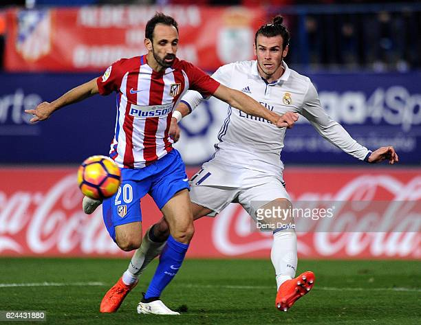 Gareth Bale of Real Madrid CF is blocked by Juanfran of Club Atletico de Madrid during the La Liga match between Club Atletico de Madrid and Real...