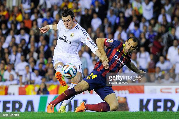 Gareth Bale of Real Madrid CF shoots towards goal under a challenge by Javier Mascherano of FC Barcelona during the Copa del Rey Final between Real...