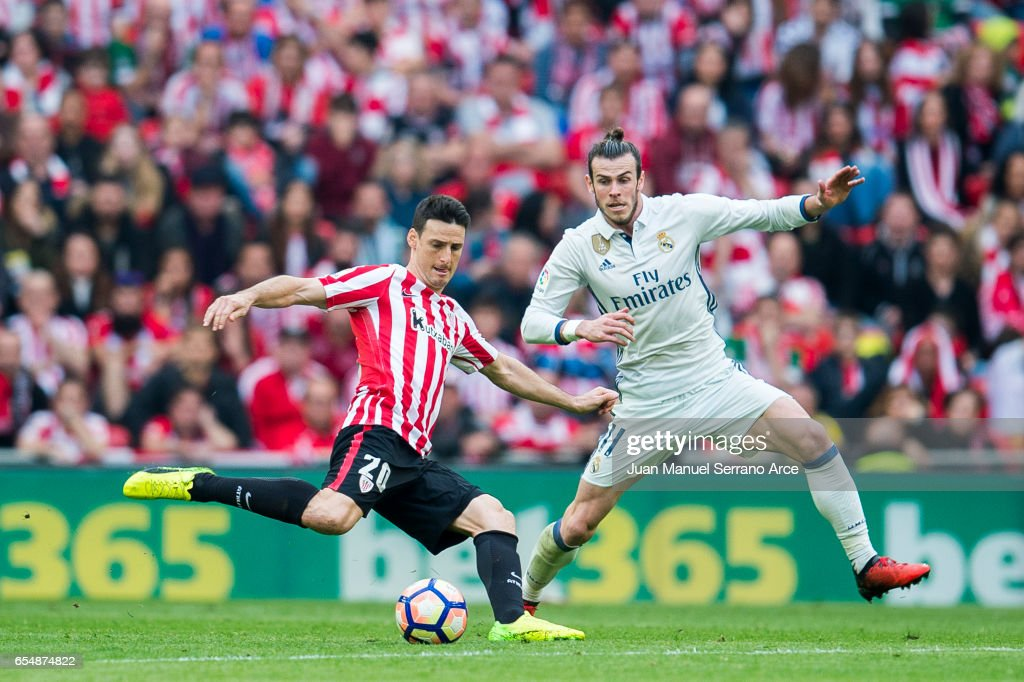 Gareth Bale of Real Madrid competes for the ball with Aritz Aduriz of Athletic Club during the La Liga match between Athletic Club Bilbao and Real Madrid at San Mames Stadium on on March 18, 2017 in Bilbao, Spain.