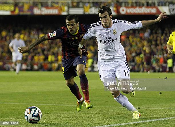 Gareth Bale of Real Madrid competes for the ball with Daniel Alves of FC Barcelona during the Copa del Rey Final between Real Madrid and Barcelona at...
