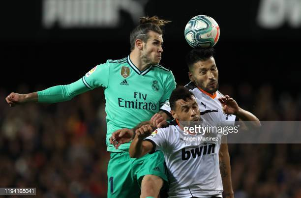 Gareth Bale of Real Madrid competes for the ball with Ezequiel Garay and Francis Coquelin of Valencia during the Liga match between Valencia CF and...