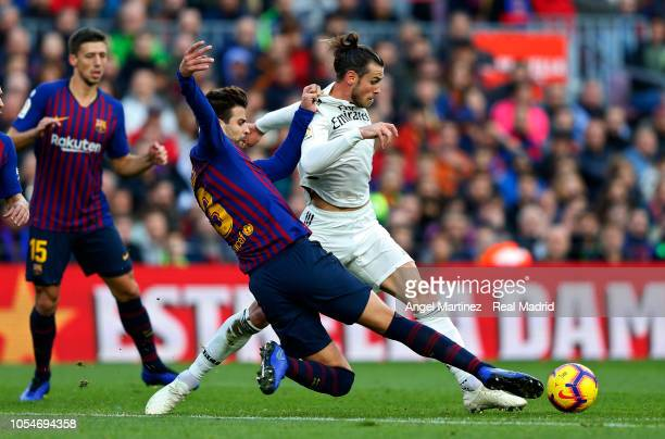 Gareth Bale of Real Madrid competes for the ball with Gerad Pique of FC Barcelona during the La Liga match between FC Barcelona and Real Madrid CF at...