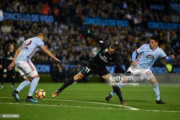 Gareth Bale of Real Madrid competes for the ball with Gustavo Cabral and Facundo Roncaglia of Celta de Vigo during the La Liga match between Celta de...
