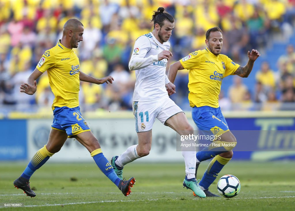 Gareth Bale of Real Madrid competes for the ball with Javi Castellano (R) and Alejandro Galvez of UD Las Palmas during the La Liga match between UD Las Palmas and Real Madrid at the Gran Canaria stadium on March 31, 2018 in Las Palmas, Spain.