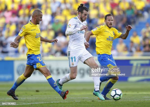 Gareth Bale of Real Madrid competes for the ball with Javi Castellano and Alejandro Galvez of UD Las Palmas during the La Liga match between UD Las...