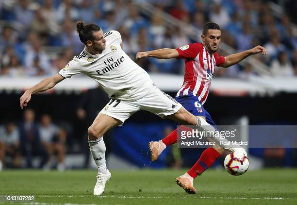 Gareth Bale of Real Madrid competes for the ball with Koke of Atletico de Madrid during the La Liga match between Real Madrid and Atletico de Madrid...