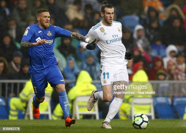 Gareth Bale of Real Madrid competes for the ball with Vitorino Antunes of Getafe during the La Liga match between Real Madrid and Getafe at Estadio...