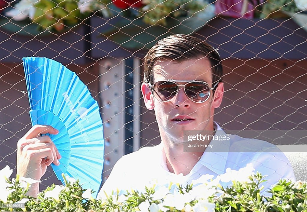 Gareth Bale of Real Madrid cools down with a fan as he watches Rafael Nadal of Spain plays Tomas Berdych of Czech Republic during day seven of the Mutua Madrid Open tennis tournament at the Caja Magica on May 9, 2014 in Madrid, Spain.