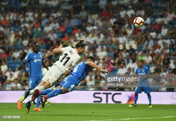 Gareth Bale of Real Madrid heads the ball while being challenged by Bruno Gonzalez of Getafe during the La Liga match between Real Madrid CF and...