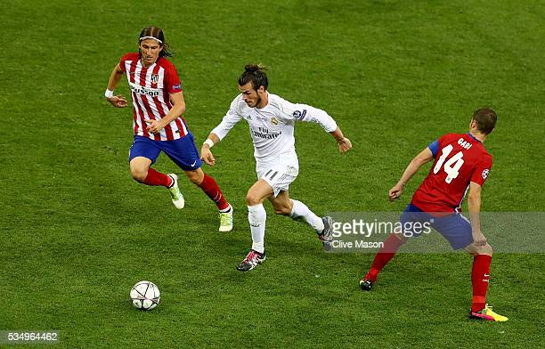 Gareth Bale of Real Madrid is challenged by Filipe Luis of Atletico Madrid during the UEFA Champions League Final match between Real Madrid and Club...