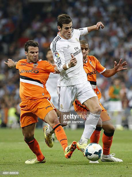 Gareth Bale of Real Madrid is challenged by Juan Bernat and Sofiane Feghouli of Valencia CF during the La Liga match between Real Madrid and Valencia...
