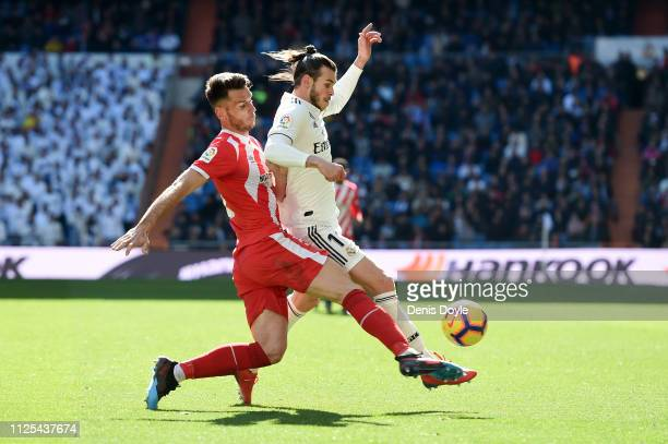 Gareth Bale of Real Madrid is challenged by Pedro Alcala of Girona during the La Liga match between Real Madrid CF and Girona FC at Estadio Santiago...
