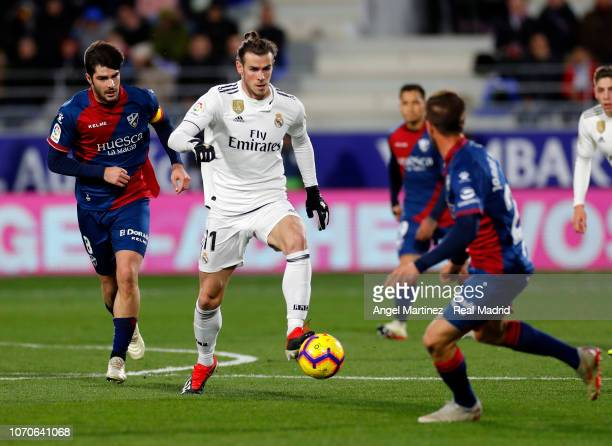 Gareth Bale of Real Madrid is chased by Gonzalo Melero of SD Huesca during the La Liga match between SD Huesca and Real Madrid CF at Estadio El...