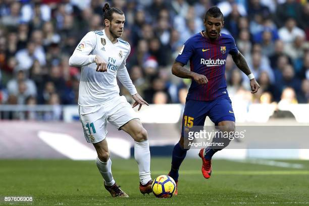 Gareth Bale of Real Madrid is chased by Paulinho of FC Barcelona during the La Liga match between Real Madrid and Barcelona at Estadio Santiago...