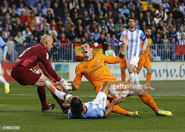 Gareth Bale of Real Madrid is fouled by Marcos Angeleri of Malaga during the La Liga match between Malaga and Real Madrid at La Rosaleda Stadium on...